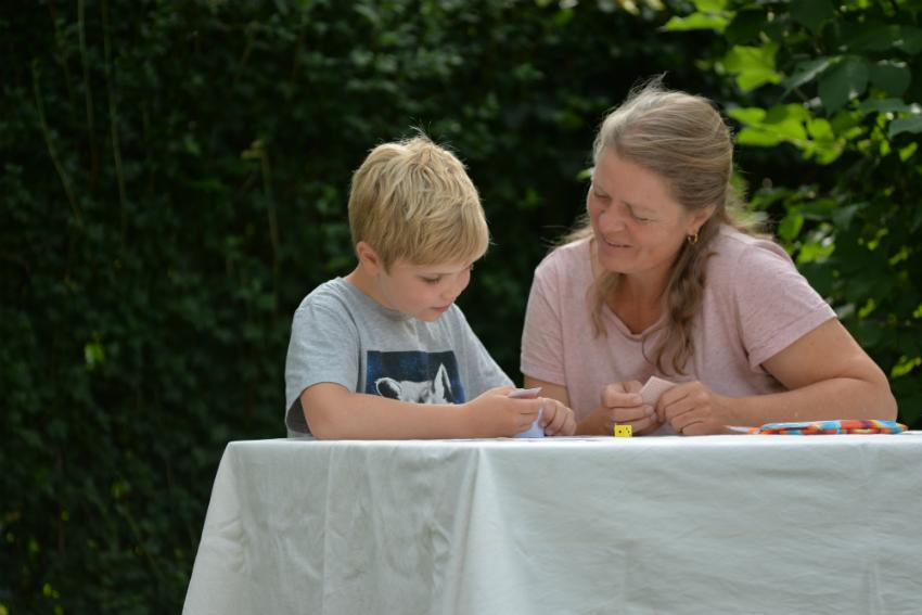 Mor og søn spiller læringsspil i haven