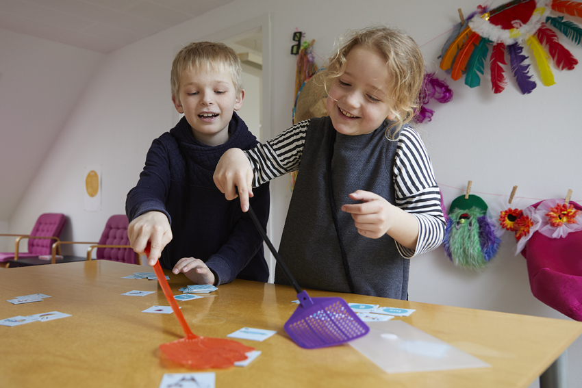 To børn spiller en læringssnack og bruger fluesmækker